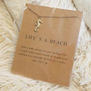 Gold tone seahorse necklace